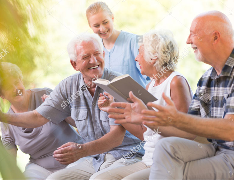 stock-photo-happy-seniors-from-nursing-house-spending-day-outside-and-reading-book-together-768854557_web